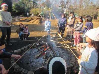 (写真)細長い篠竹の先にパン生地を巻き付けてたき火で焼いている子どもたち.jpg