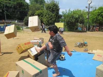 写真。積み上げたダンボールを蹴っている子ども。