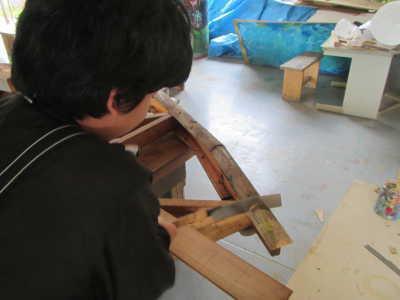 写真。木材をののこぎりで切る子ども。