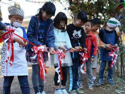 (写真)子どもたちが赤白のリボンにハサミをいれています。