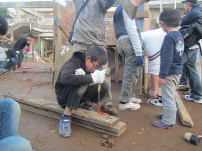 (写真)木材から釘を抜いている男子。