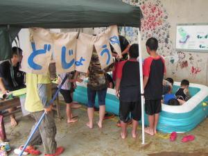 写真。「どじょう」の暖簾の向こうで、プールに泳ぐドジョウを見つめる子どもたち。