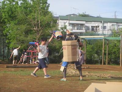 スタッフと子どもがダンボールで戦っている風景