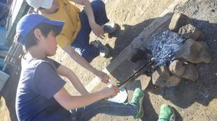 男の子がたき火をしている風景