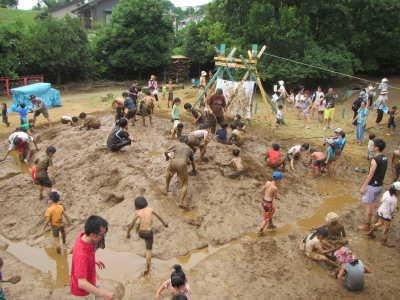 泥山で遊ぶたくさんの子どもたち