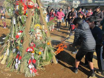 (写真)竹で組まれたどんど焼きに子どもたちが火入れする様子。