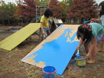 写真。木材にペンキを塗る子ども。