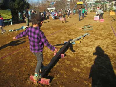 (写真)細長い棒の上をバランスをとって渡ろうとする子ども.jpg