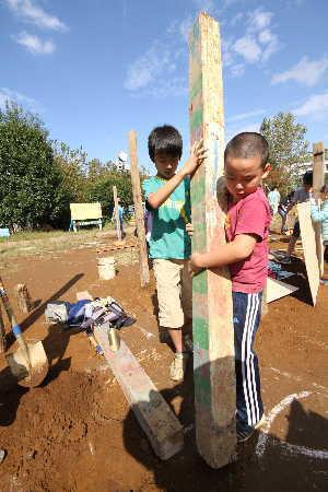 (写真)二人で協力して柱を建てる男の子たち