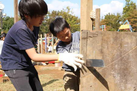 (写真)真剣な表情で板をノコギリで切る男の子