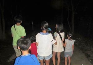 写真。暗い中、歩き出す子ども達。