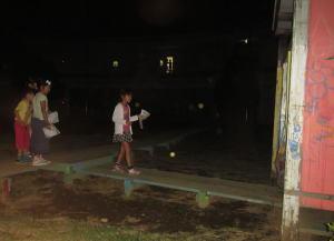 写真。暗い中、小屋に近づく子どもたち。