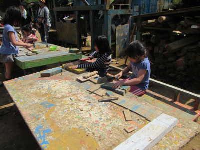 写真。木工作をしている子どもたち。
