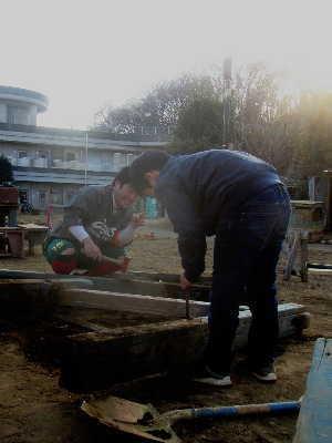 (写真)木材から釘を抜く男の子とそれを見守るスタッフ