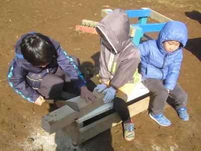 (写真)木材を協力してのこぎりで切る子ども