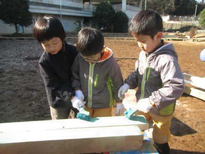 (写真)木材にペンキを塗る子どもたち