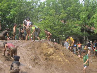 (写真)大きな土山でドロドロになりながら夢中で遊ぶ子どもたち