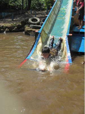 写真。ウォータースライダーから池へ水しぶきをあげて滑りおりる子どもの様子。