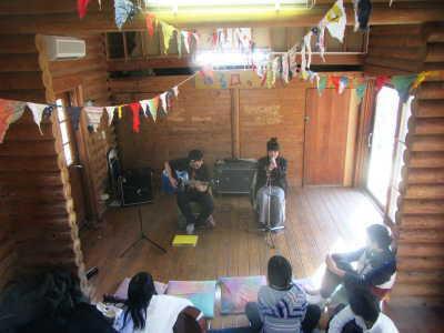 (写真)ログハウスで演奏する高校生ら。